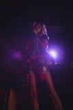 Anseende för kvinnlig sångare på upplyst etapp i nattklubb Arkivbild