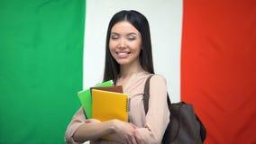 Anseende för kvinnlig student med förskriftsböcker mot italiensk flagga på bakgrund lager videofilmer