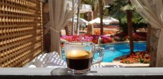 Anseende för svart kaffe på hotellfönster med sikt på utvändig pöl arkivfoton