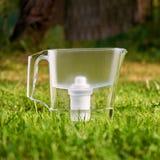 Anseende för tillbringare för vattenfilter på det gröna gräset i sommarträdgård royaltyfria bilder