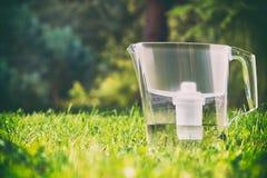 Anseende för tillbringare för vattenfilter på det gröna gräset i sommarträdgård royaltyfri fotografi