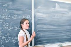 Anseende för tonårs- flicka och svara på svart tavla i matematikgrupp Utbildning tillbaka till skolabegreppet, kopieringsutrymme arkivfoton