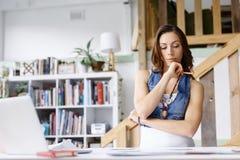 Anseende för ung kvinna i idérikt kontor Royaltyfria Bilder