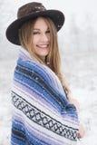 Anseende för ung kvinna i snö med den bohemiska den stilhatten och filten Arkivbild