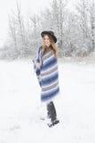 Anseende för ung kvinna i snö med den bohemiska den stilhatten och filten Royaltyfri Foto