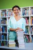 Anseende för ung kvinna mot bokhyllan i arkiv royaltyfri bild