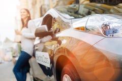 Anseende för ung kvinna nära bilen med den konvexa pannlampan Royaltyfri Fotografi