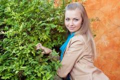 Anseende för ung kvinna nära en grön häck Royaltyfri Fotografi