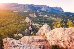 Anseende för ung kvinna på bergmaximumet på solnedgången Fotografering för Bildbyråer