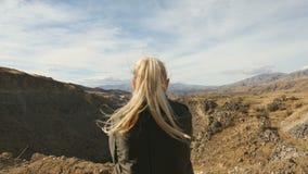 Anseende för ung kvinna på kanten av klippan och att lyfta henne händer upp mot höga steniga berg som in solbadar lager videofilmer