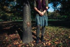 Anseende för ung kvinna vid ett träd i höst Royaltyfri Fotografi