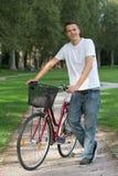Anseende för ung man bredvid hans cykel arkivfoto