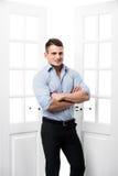 Anseende för ung man för stående tillfälligt i dörröppningshemmiljön på ljus bakgrund som ler och ser till kameran med Royaltyfria Foton
