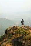 Anseende för ung man på överkanten av ett berg och att tycka om dalsikt Royaltyfria Foton