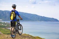 Anseende för ung man på berget med cykeln arkivfoton