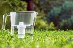 Anseende för vattenfiltreringkanna på det gröna gräset i sommarträdgård royaltyfria foton