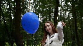 Anseende f?r ung kvinna och spela med en ballong i en skog i v?r arkivfilmer