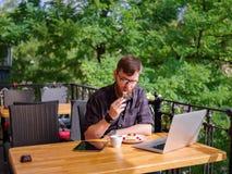 Ansenlig ung man som arbetar på minnestavlan, medan sitta utomhus äganderätt för home tangent för affärsidé som guld- ner skyen t Arkivfoton
