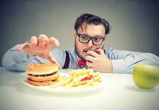 Ansia maciza del hombre para los alimentos de preparación rápida Foto de archivo