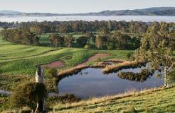 Ansicht über Ackerland mit Bäumen und eine Verdammung, nebelhafte Hügel entlang dem Horizont Lizenzfreie Stockbilder
