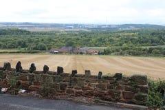 Ansicht über Ackerland zum Bauernhof Stockbild