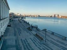 Ansicht über alte geschlossene Fluss-Station in Kiew und die Leute, die auf Damm von Dnipro-Fluss gehen stockfoto