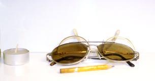 Ansicht über alte Sonnenbrille und eine Kerze mit weißem Hintergrund Lizenzfreie Stockbilder