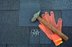 Ansicht über Asphalt Roofing Shingles Background Dach-Schindeln - Deckung Asphalt Roofing Shingles Hammer, Handschuhe und Nägel stockbild
