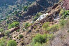 Ansicht über das felsige Tal von Gran Canaria mit traditioneller Wohnung und dem Eingang zum Höhlenhaus stockfotografie