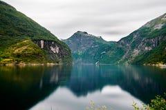 Ansicht über das Geirangerfjord mit Wasser im Vordergrund und den Bergen im Hintergrund Lizenzfreie Stockbilder