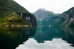 Ansicht über das Geirangerfjord mit Wasser im Vordergrund und den Bergen im Hintergrund Stockfoto