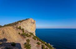 Ansicht über den enormen Felsen bedeckt mit wenigen kleinen Bäumen über Schwarzem Meer Stockfoto