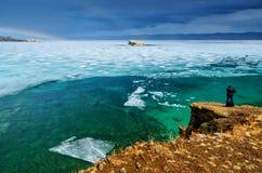 Ansicht über den großen schönen Baikalsee mit den Eisschollen, die auf das Wasser und die Männer zurück schwimmen, macht Fotos, R Stockbild