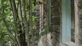 Ansicht über die Fassade des alten zerstörten verlassenen Holzhauses im Dorf stock footage