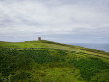 Ansicht über die Hügel und einen Altbau nahe dem Meer in Donegal Stockfotos
