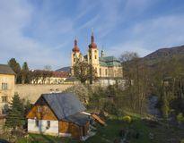 Ansicht über Dorf Hejnice mit den Häuschen, Nebenfluss und barocker Basilikakirche von VisitationJungfrau Maria im Frühjahr, gold stockfotos