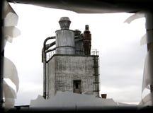 Ansicht über ein altes Industriegebäude durch ein Fenster Lizenzfreie Stockfotos