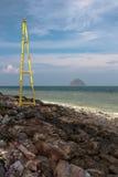 Ansicht über eine kleine Insel vom felsigen Ufer mit einem Leuchtturm in Thailand Stockbilder