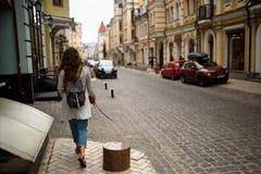 Ansicht über eine Stadtstraße mit der Frau, die auf einen Bürgersteig geht Lizenzfreie Stockbilder