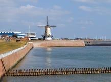 Ansicht über einen Hafen mit den alten und modernen Windmühlen stockfotografie