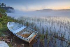 Ansicht über nebeligen See mit Booten auf dem Ufer Stockfotografie