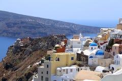 Ansicht über Santorini, das bunte Gebäude betrachtet, wölben sich Kirchen mit Berg und Meer im Hintergrund lizenzfreie stockfotografie