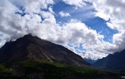 Ansicht ?ber den H?gel mit Gebirgspfad und die schneebedeckten Berge auf dem Hintergrund stockfotos