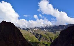 Ansicht ?ber den H?gel mit Gebirgspfad und die schneebedeckten Berge auf dem Hintergrund stockfoto
