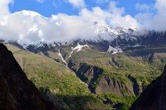 Ansicht ?ber den H?gel mit Gebirgspfad und die schneebedeckten Berge auf dem Hintergrund lizenzfreie stockfotografie