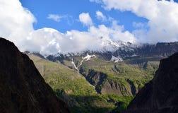 Ansicht ?ber den H?gel mit Gebirgspfad und die schneebedeckten Berge auf dem Hintergrund stockbilder