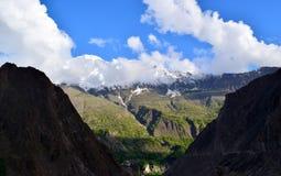 Ansicht ?ber den H?gel mit Gebirgspfad und die schneebedeckten Berge auf dem Hintergrund lizenzfreie stockfotos