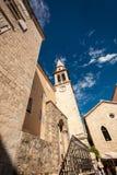 Ansicht der alten schmalen Straße mit hohem Glockenturm lizenzfreie stockfotografie