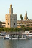 Ansicht der Ausflugboote und des achteckigen Turms von Torre Del Oro macht goldene Reflexion auf Canal de Alfonso von Rio Guadalq Stockfotos