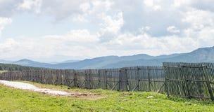 Ansicht der Berge hinter dem Zaun vom Durchlauf Lizenzfreies Stockfoto